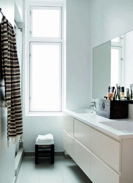 Small Scandinavian bathroom with large window and cupboards without handle